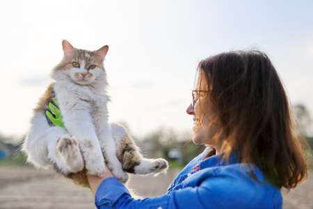 Outdoor woman holding domestic cat in arms and talking to her, friendship of the owner and pet