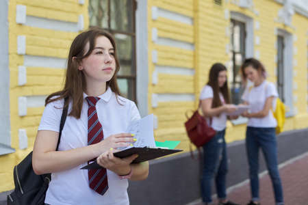 Girl teenager college student posing outdoor in white T-shirt with tie. Background brick building, group of girls students. Beginning of classes, back to college, copy space