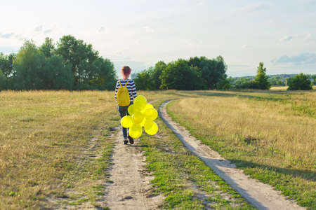 Teenager girl with backpack and yellow balloons running on country road, rear view. Happy girl walking forward, sky in the clouds, meadow, nature background Stock fotó