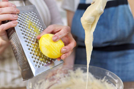 Closeup of woman rubbing lemon zest on grater, female preparing dough for muffins. Standard-Bild