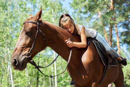 Girl child riding horse, summer horse ride in the forest, girl lovingly hugged horse.