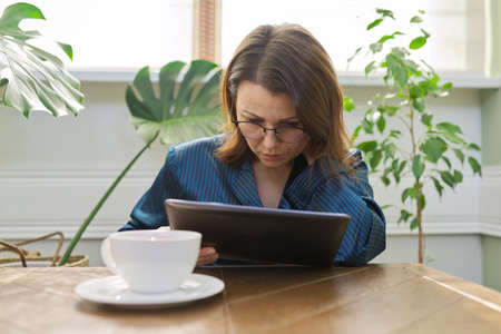 Serious mature woman having breakfast at home in pajamas with cup of tea sitting at table reading digital tablet. Sad female from read mail, news. Negative emotions, information, life of middle-aged