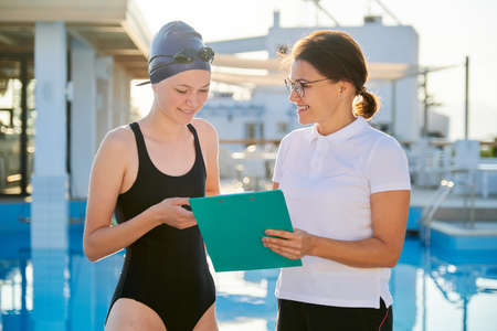 Girl teenager swimmer in sports swimsuit cap with woman trainer near outdoor pool, active healthy lifestyle of youth