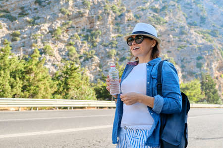 Woman in hat with bottle of water in mountains on highway, hitchhiking, stopping the bus, with copy space. Nature, road, tourism, travel, adventure, road trip concept background