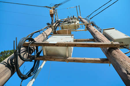 Electric transformer on wooden poles, blue sky background. 写真素材