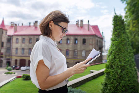 Portrait of mature businesswoman teacher, manager with business papers documents in hands. School building, office building background, professional confident female with glasses white shirt