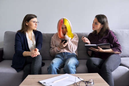 Woman social worker talking to mother and daughter teenage girl. Professional advice, help, support. Psychology, therapy, adolescence, family, mental health conceptt Standard-Bild