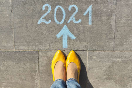 2021 year arrow forward concept, top view on woman legs and text written in chalk on gray sidewalk