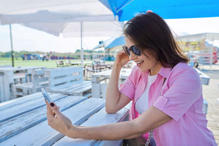 Adult woman making a video call on a smartphone sitting at a table in a summer outdoor cafe