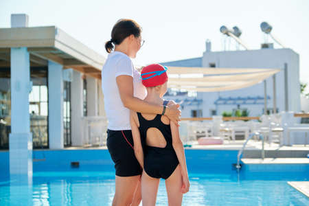 Family, sport, swimming, health, lifestyle concept. Portrait of mother and kid daughter, back view, outdoor swimming pool background, girl wearing swim goggles swimming cap preparing to swim