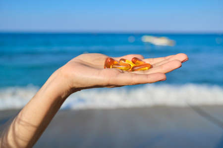 Capsule of vitamin d, e, a, omega 3, fish oil in the hand close-up. Blue sea, sky background. Healthy eating, medicine, lifestyle, nutritional supplements concept