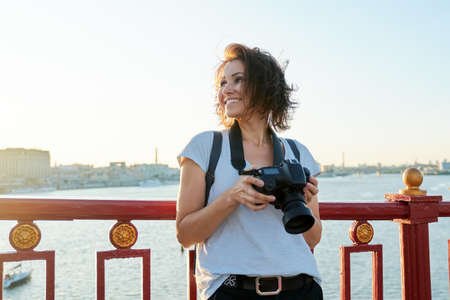 Mature female photographer with professional camera and backpack, smiling female on the bridge on sunny sunset summer day. River, sky, city skyline background