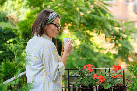 Portrait of middle-aged woman relaxing on an open landscaped balcony with cup of coffee, woman enjoying on terrace with plants, copy space