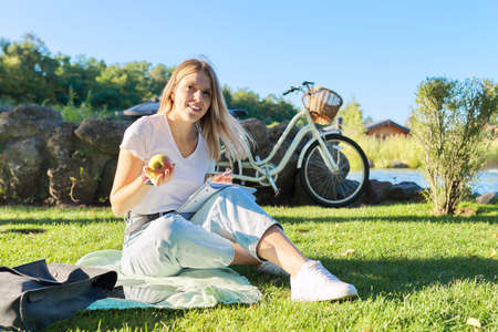 Happy beautiful girl student sitting on grass in park with apple, notebook, smartphone, bicycle. Active healthy lifestyle of youth, education lifestyle of adolescents, copy space