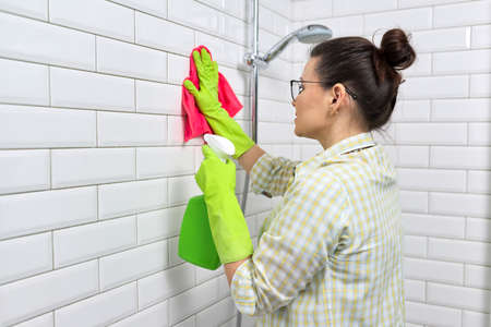 Bathroom cleaning, housewife washing white tile wall with detergent and rag, copy space. Hygiene, purity, cleanliness concept