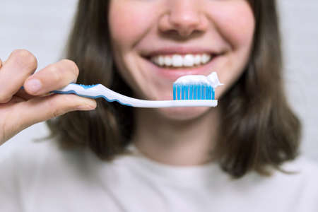 Close-up of teenager girl with toothpaste on brush brushing her teeth in the bathroom, morning and evening dental hygiene