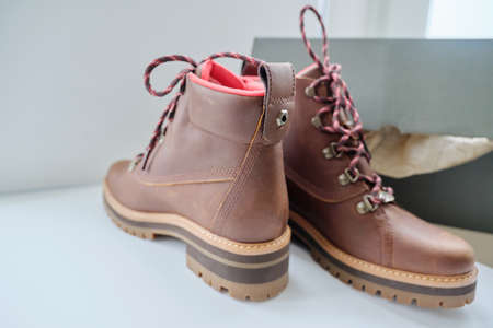 New womens leather brown waterproof hiking winter autumn boots in a box, trendy footwear for winter. Unpacking boots, shopping online from home, shoe fashion store