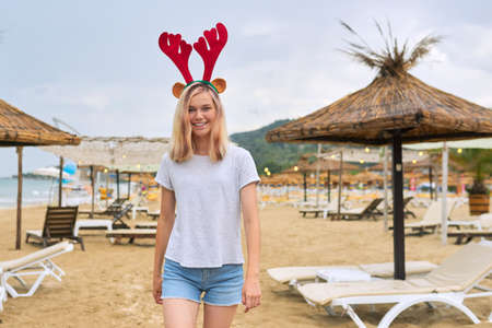 Beautiful smiling happy young woman, teenage girl walking on the beach in Christmas deer ears. New Year holidays, vacations, travel, tourism concept