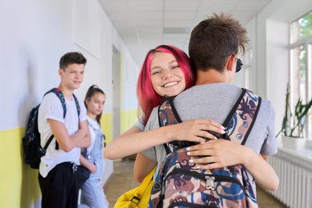 Hugging greeted teenagers at school, happy smiling face of girl hugging boy, students corridor school building