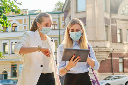 Office workers two young business women walking along the city street wearing medical protective masks. Lifestyle, business in an epidemic, pandemic, bad ecology
