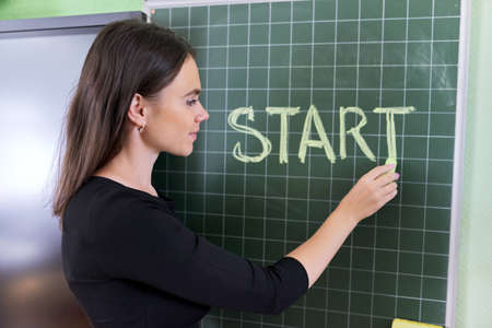 Back to school, back to college, woman teacher writes in chalk on blackboard word start Фото со стока