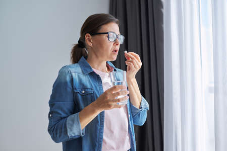 Mature middle-aged woman in casual clothes at home holding pill and glass of fresh water. Headaches, depression, medicine supplements vitamins, sedatives, menopause