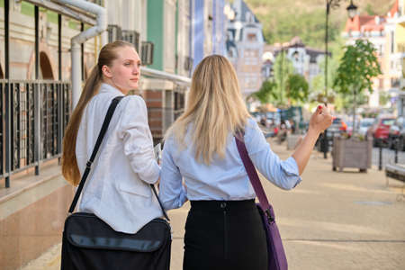 Back shot of two young business women walking and talking in the city, female office employees