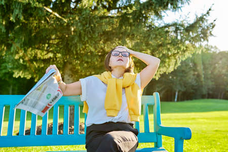 Symptoms of menopause in mature woman, female waves newspaper to cool off, feels hot, age hormonal changes. Woman on bench in the park