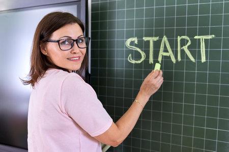 Back to school, back to college, woman teacher writes in chalk on blackboard word start