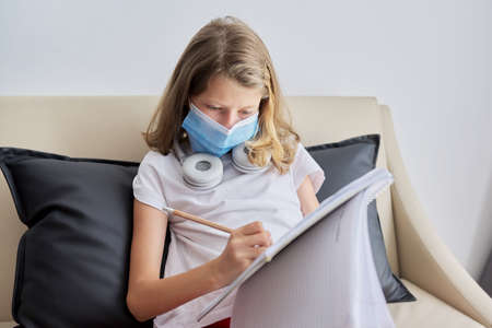 Girl child 9, 10 years old in protective medical mask on her face studies while sitting on couch, student writes and reads in notebook, individual private lessons