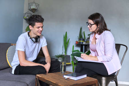 Boy teenager gives interview to woman psychologist in office, college student at consultation. Adolescence, mental health, social life of teenager