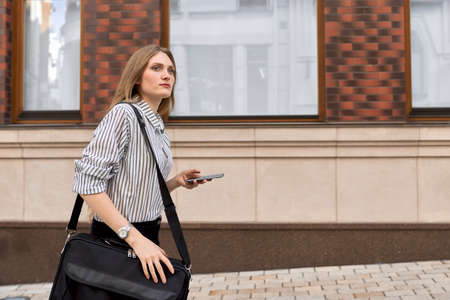 Young business woman walking with cellphone along city street, profile view, brick building background copy space