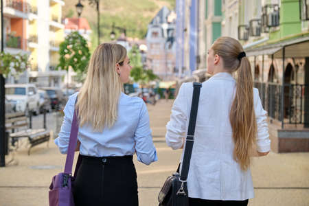 Business people, two young businesswomen, office workers walking with their backs along city street.