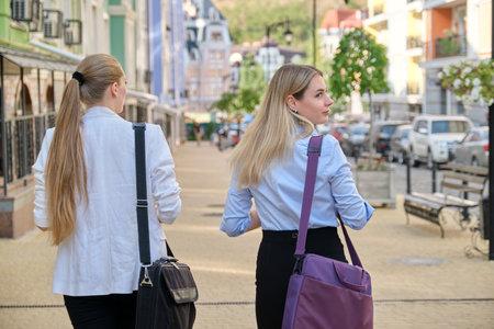 商界人士,两个年轻的女企业家,办公室工作者走在城市街道上。