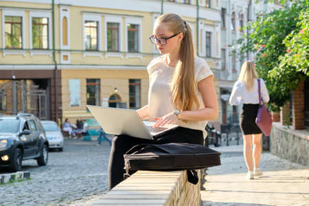 Young businesswoman sitting with laptop looking at the screen, working outdoors. City, freelance, business, lifestyle concept, street business people background
