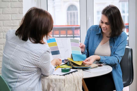 Interior design, working women designers choosing samples of fabrics and accessories for curtains