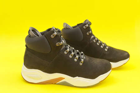 New womens leather black waterproof hiking winter autumn boots on yellow background, trendy footwear for winter. Online shopping from home, shoe fashion store