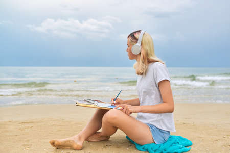 Teenagers, creative talented youth, teenager girl in headphones drawing with watercolors marine sketch, female sitting on sea beach, beautiful water landscape background