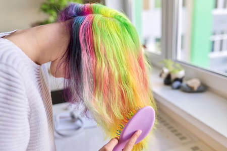 Fashionable teen girl with trendy rainbow dyed long hair combing her hair at home. Hair, hairstyles, coloring fashion, youth and beauty