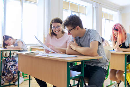 Lesson in the class of high school students, female teacher sitting at desk with male student teenager.