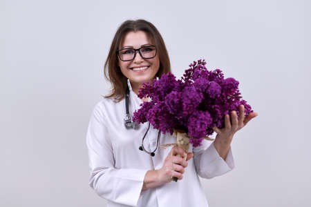 Bouquet of lilac flowers in the hands of female doctor with stethoscope. World health day, happy nurse with flowers on grey background