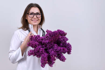 Portrait of female doctor with stethoscope with bouquet of lilac flowers. World health day, happy nurse with flowers on grey background, copy space