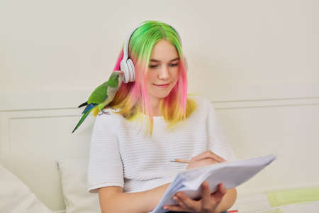 Bright beautiful owner of a parrot teenager student with a pet on her shoulder. Trendy dyed hair girl with headphones writing in a school notebook