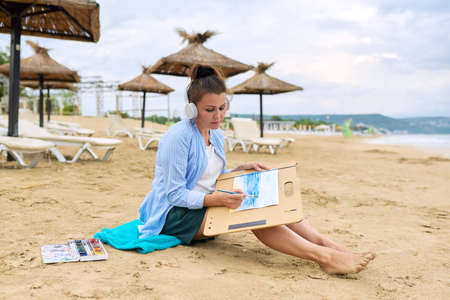 Mature woman in headphones sitting on sandy beach drawing sketch of sea nature with watercolors. Rest, relaxation, hobbies and leisure, creativity, mental health, middle-aged people