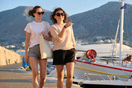 Sea family vacation together, happy mom and teenage daughter walking along the pier. Sea, moored boats, mountains, sunset background