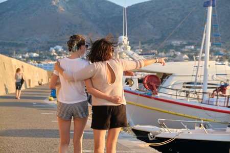 Sea family vacation together, happy mom and teenage daughter walking along the pier, women hugging back view. Sea, moored boats, mountains, sunset background Imagens