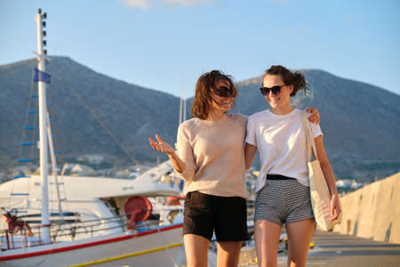 Sea family vacation together, happy mom and teenage daughter walking along the pier, women hugging. Sea, moored boats, mountains, sunset background Imagens