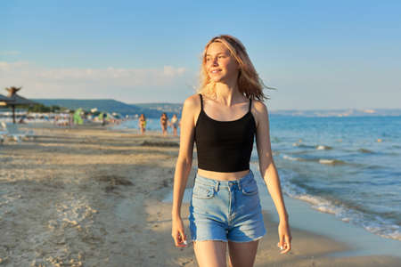 Beautiful happy female teenager 16 years old walking along sea sandy beach, at sunset time, tanned blonde girl with wet hair in top and denim shorts