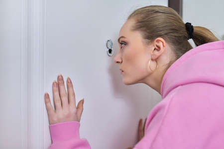 Young woman looking through the peephole of front door in apartment.