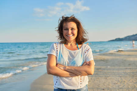 Portrait of happy smiling confident middle aged woman on beach